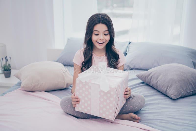 关闭美丽的照片她她的女孩坐的床星期天周末早晨得到大giftbox父母意想不到 免版税图库摄影