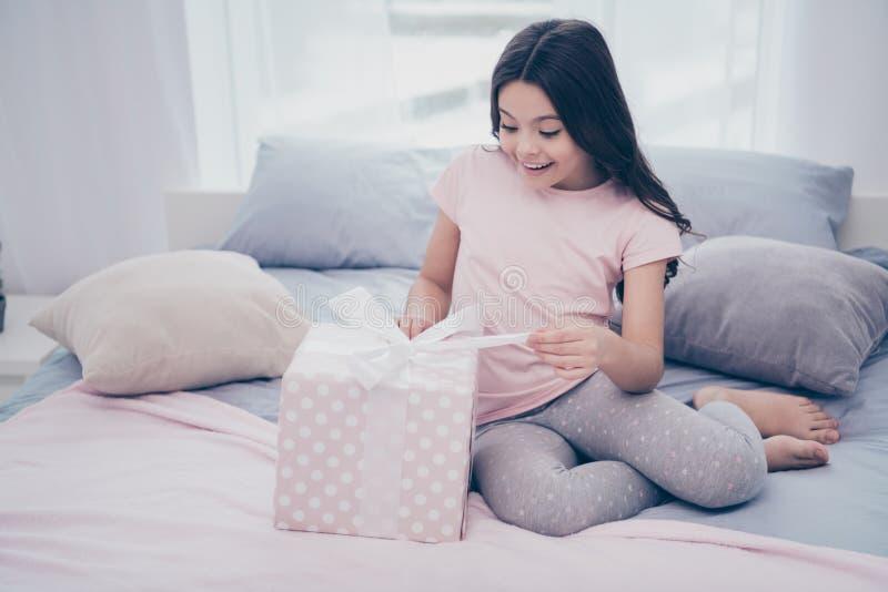 关闭美丽的照片她她的女孩坐的床星期日早晨举行打开的当前箱子最佳的天佩带在家 免版税库存图片