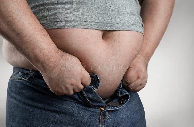 关闭设法超重的人穿小牛仔裤 免版税库存照片