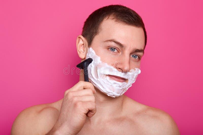 关闭英俊的赤裸上身的人站起来隔绝在桃红色背景 有赤裸肩膀的人拿着剃刀 男孩剃并且 免版税库存图片