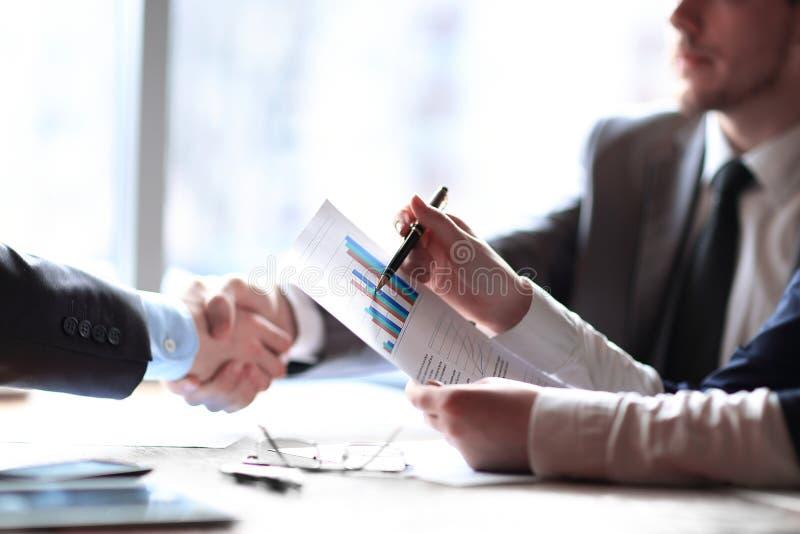 关闭 企业握手书桌的商人 到达天空的企业概念金黄回归键所有权 库存照片