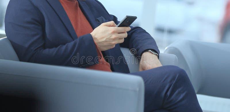 关闭 使用坐在大厅的手机的商人 免版税库存照片