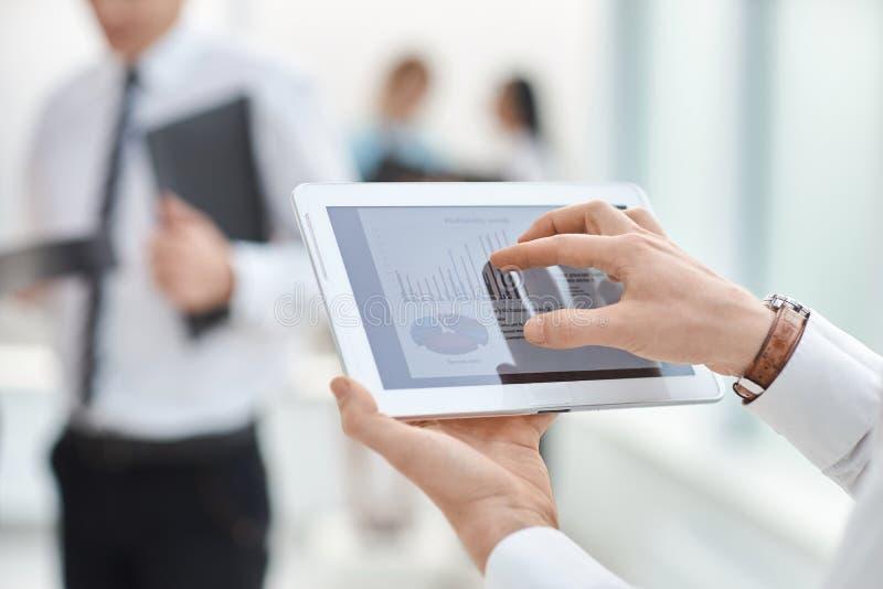 关闭 商人使用一种数字片剂检查财务数据 库存照片