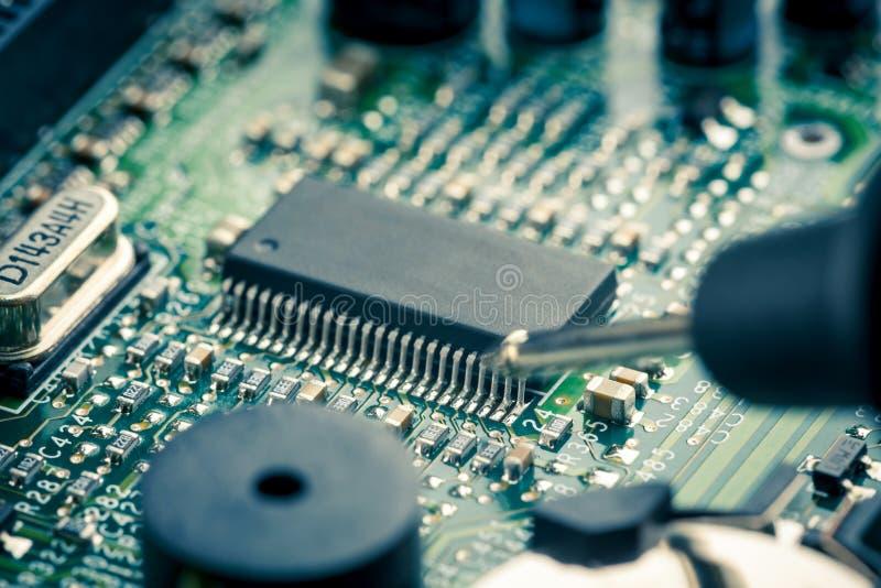 关闭-技术员工程师测量的多用电表计算机电路板主板 免版税库存照片