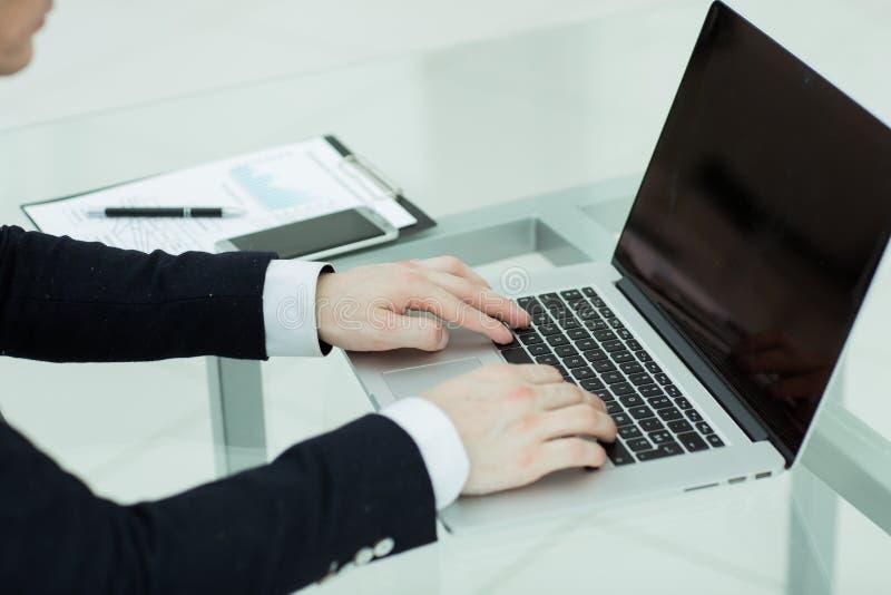 关闭 背景生意人膝上型计算机键入的空白年轻人 免版税库存图片