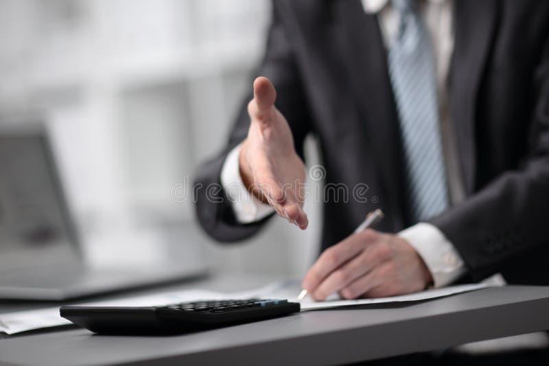 关闭 致以他的手的商人对商务伙伴 免版税库存图片