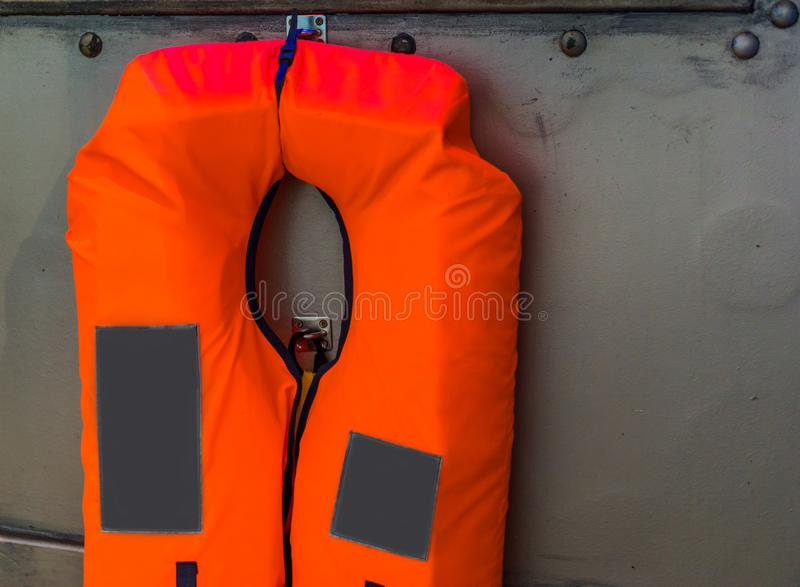典型的橙色救生衣垂悬在金属墙壁上的,水交通安全,海洋背景 库存图片