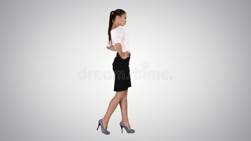典雅成套装备走的美丽的年轻女人,握在臀部的手在梯度背景 免版税图库摄影