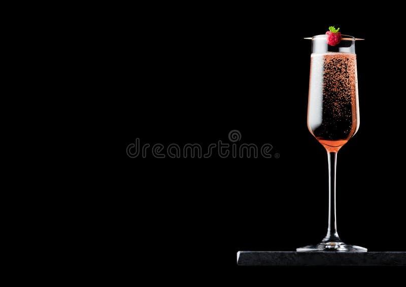 典雅的杯桃红色玫瑰色香槟用在棍子的莓在黑背景的黑人大理石委员会 文本的空间 库存图片