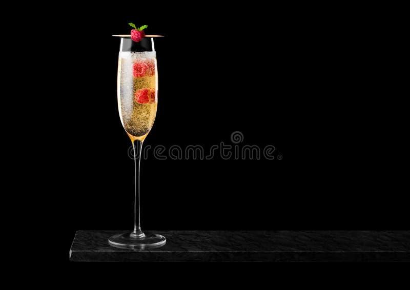 典雅的杯黄色香槟用莓和泡影在黑人大理石委员会里面黑背景的 图库摄影