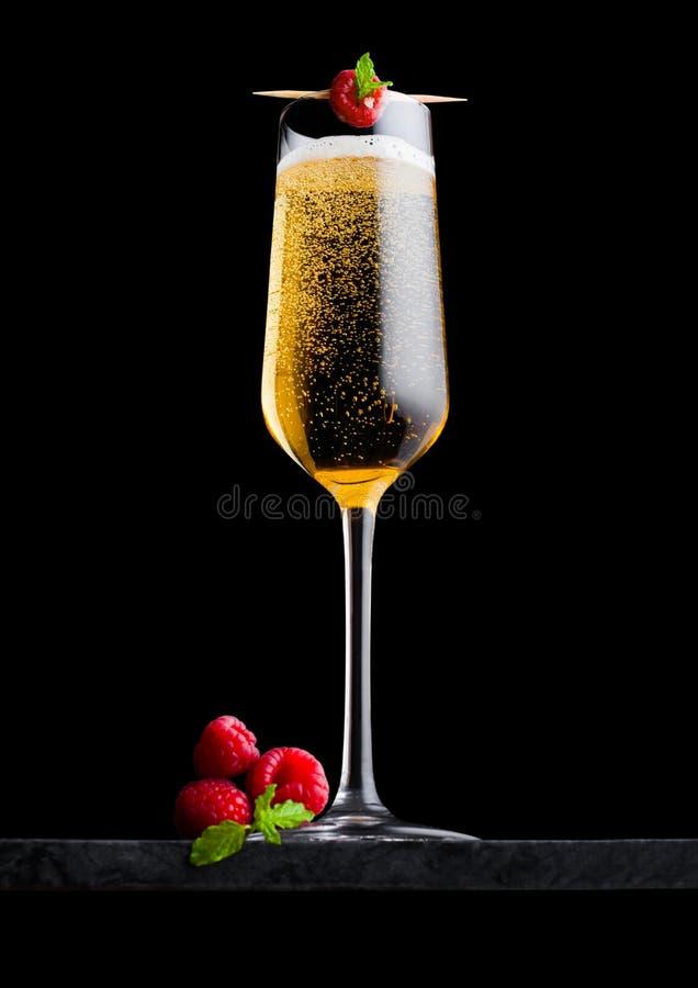 典雅的杯黄色香槟用莓和新鲜的莓果与薄荷的叶子在棍子在黑人大理石委员会 免版税图库摄影