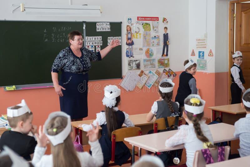 典雅的第一辆平地机坐在书桌和神色在从类出来的老师和男孩在小学 免版税库存照片