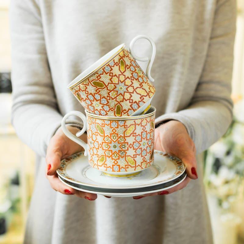 典雅的茶或咖啡茶杯在妇女的手上 妇女拿着陶器 库存图片