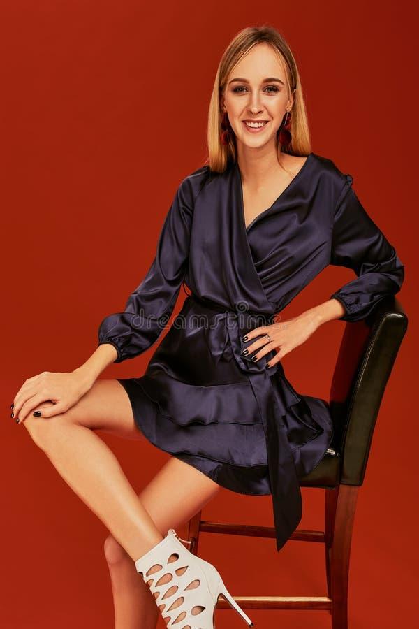 典雅的黑燕尾服的美丽的年轻白肤金发的妇女为倾斜在椅子的照相机摆在 库存图片
