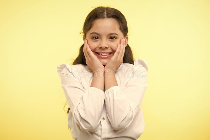 充分兴奋 女孩愉快的微笑的面孔接触她的面颊黄色背景 女小学生不可能等待对回到 图库摄影