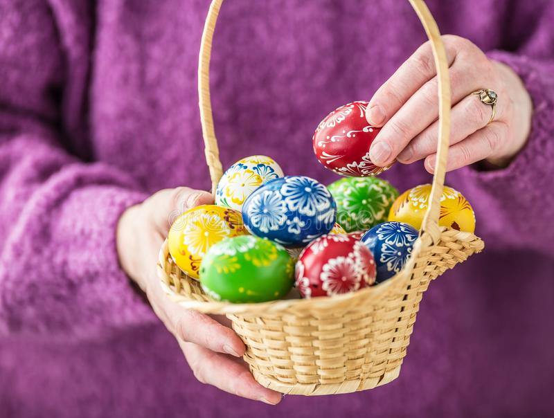 充分篮子在手领抚恤金者妇女的多彩多姿的复活节彩蛋 免版税库存图片