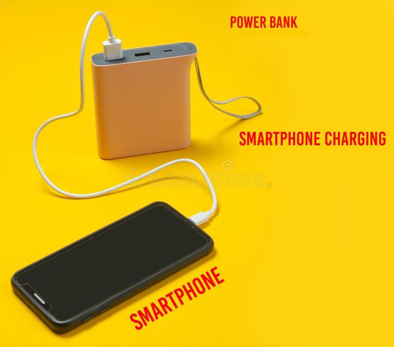 充电与力量银行的现代智能手机在黄色背景 图库摄影