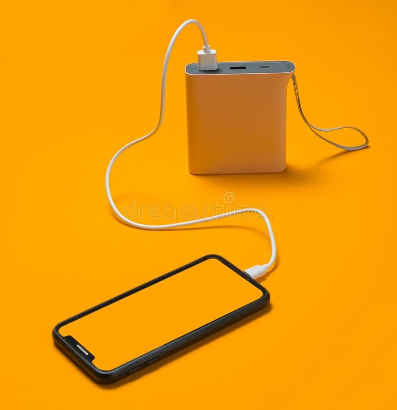 充电与力量银行的现代智能手机在黄色背景 免版税库存照片