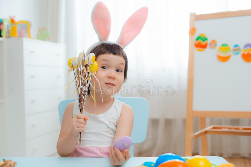 兔宝宝耳朵的女孩使用用复活节彩蛋 庆祝复活节的孩子 免版税图库摄影