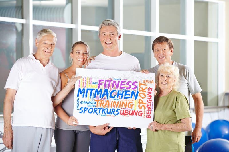 前辈在健身俱乐部拿着海报 库存照片