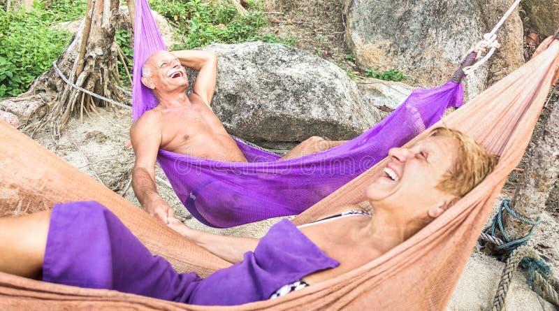 前辈放松在吊床的退休的夫妇度假者在海滩-活跃年轻的老人和愉快的旅行概念在游览中  免版税库存图片