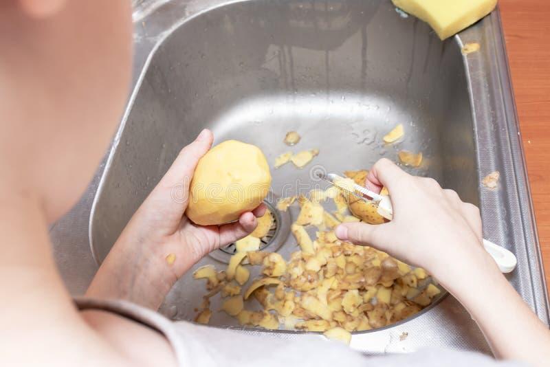 剥与一把剥的刀子的少年男孩的手土豆在厨房里帮助父母-做家庭作业和烹调的孩子 免版税库存图片