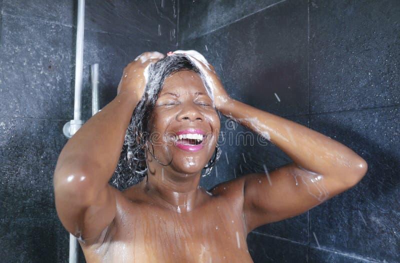 国内生活方式画象年轻愉快和美好黑非裔美国人妇女微笑愉快在家洗澡 免版税库存图片