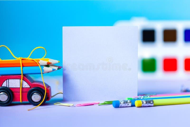 回到概念学校 学校和办公用品,五颜六色的笔,铅笔,在蓝色背景的油漆 库存图片