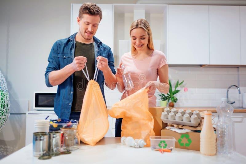 回收 投入空的塑料和纸的负责任的年轻家庭在袋子,当站立在桌附近填装了与时 免版税库存照片