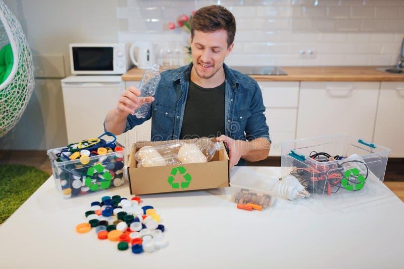 回收 放emty塑料瓶的年轻微笑的人入纸箱,当坐在与其他废物的桌上在时 免版税库存照片