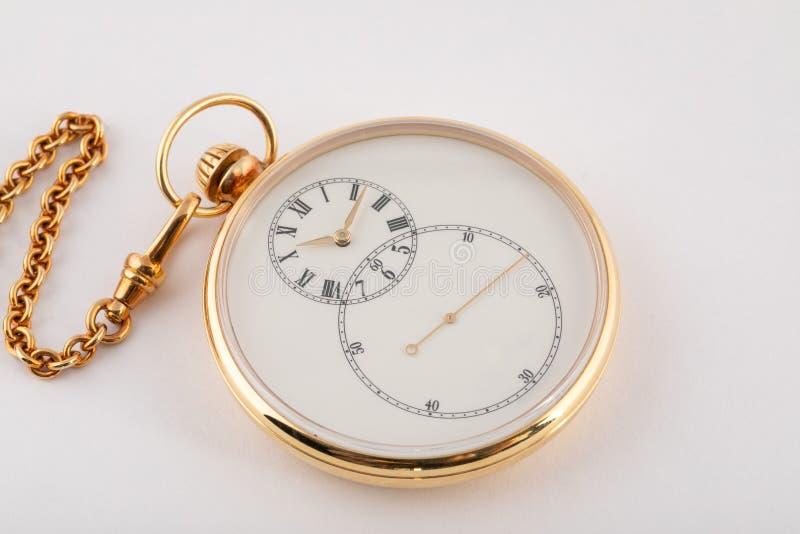 围绕手扶,有白色拨号盘和黑数字的金色调的手表和在白色背景隔绝的金链子的金手 免版税图库摄影