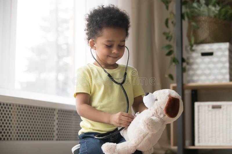 Śliczna afrykańska chłopiec bawić się z zabawką jako doktorski mienie stetoskop zdjęcia stock