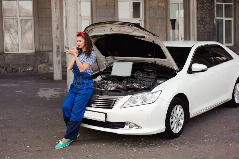 Śliczna atrakcyjna dziewczyna egzamininuje samochodowego silnika przy auto remontowym sklepem zdjęcie royalty free