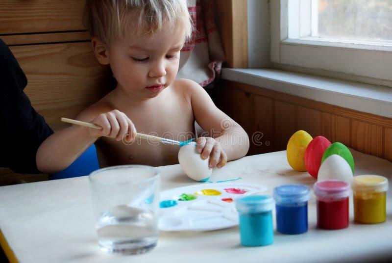 Śliczna blond chłopiec farbuje Wielkanocnych jajka w domu Szczera fotografia z naturalnym światłem zdjęcia royalty free