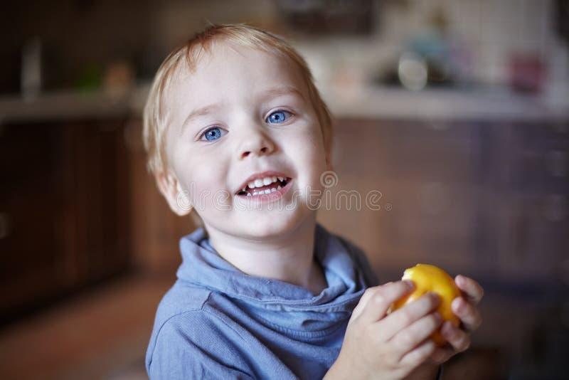 Śliczna caucasian chłopiec z niebieskimi oczami i blondynka włosy je żółtego jabłka, trzymający je na rękach, ono uśmiecha się obrazy royalty free