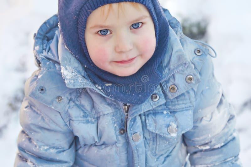 Śliczna caucasian liittle chłopiec z jaskrawymi niebieskimi oczami w zima odzieżowym i kapeluszowym kapiszonie na zimy tle Zdrowy zdjęcia stock