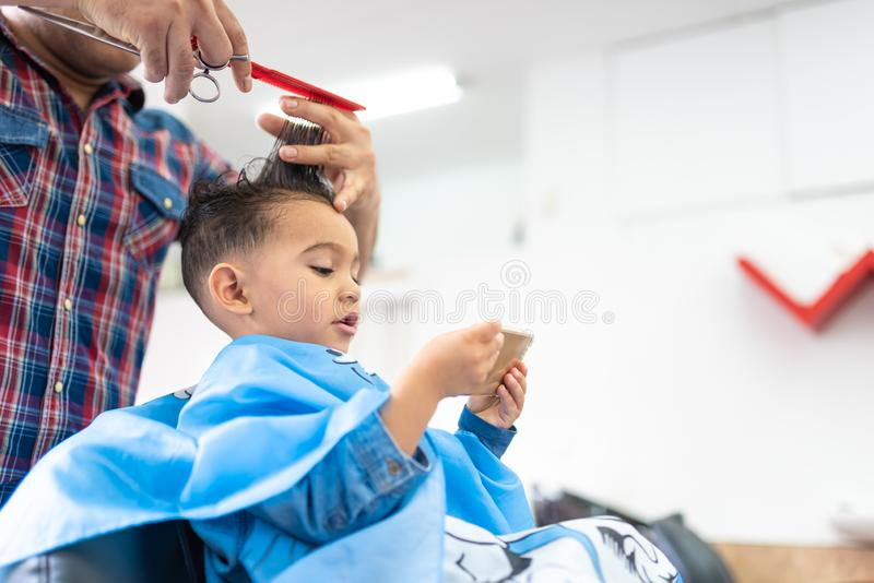Śliczna chłopiec Dostaje włosy Ciący w fryzjera męskiego sklepie tła piękna błękitny pojęcia zbiornika kosmetyczny głębii szczegó obrazy stock