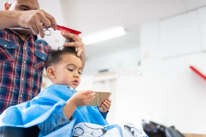 Śliczna chłopiec Dostaje włosy Ciący w fryzjera męskiego sklepie tła piękna błękitny pojęcia zbiornika kosmetyczny głębii szczegó obraz royalty free