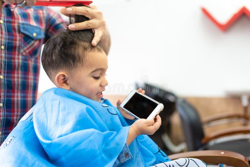 Śliczna chłopiec Dostaje włosy Ciący w fryzjera męskiego sklepie tła piękna błękitny pojęcia zbiornika kosmetyczny głębii szczegó obrazy royalty free