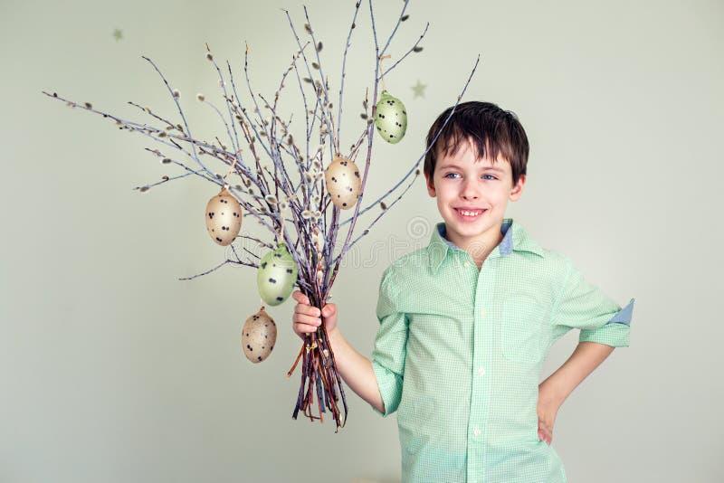 Śliczna chłopiec mienia kici wierzba kapuje z wieszać Easter jajka obraz royalty free