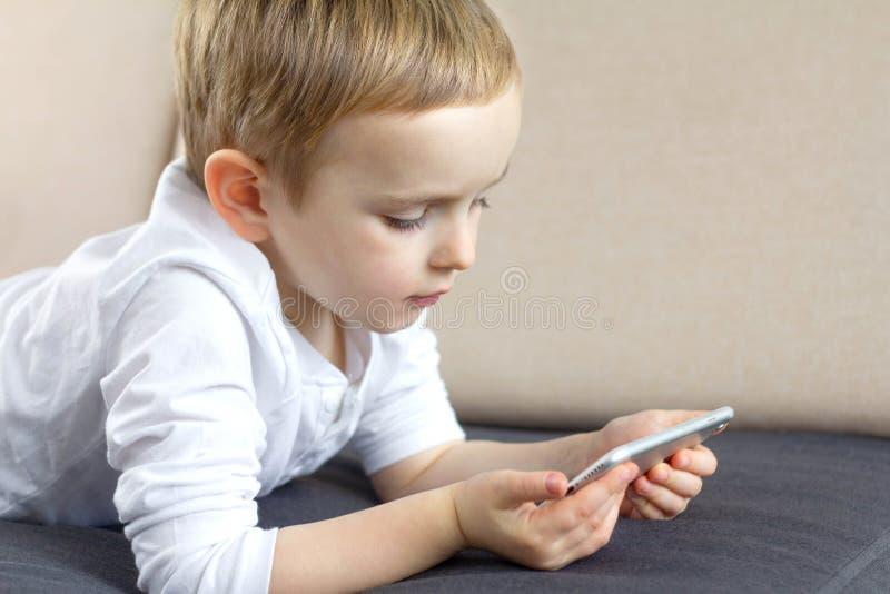 Śliczna chłopiec używa smartphone głosu zastosowanie w domu Szczęśliwy mądrze dziecko używa mobilnego app Edukacja, technologia i zdjęcia stock