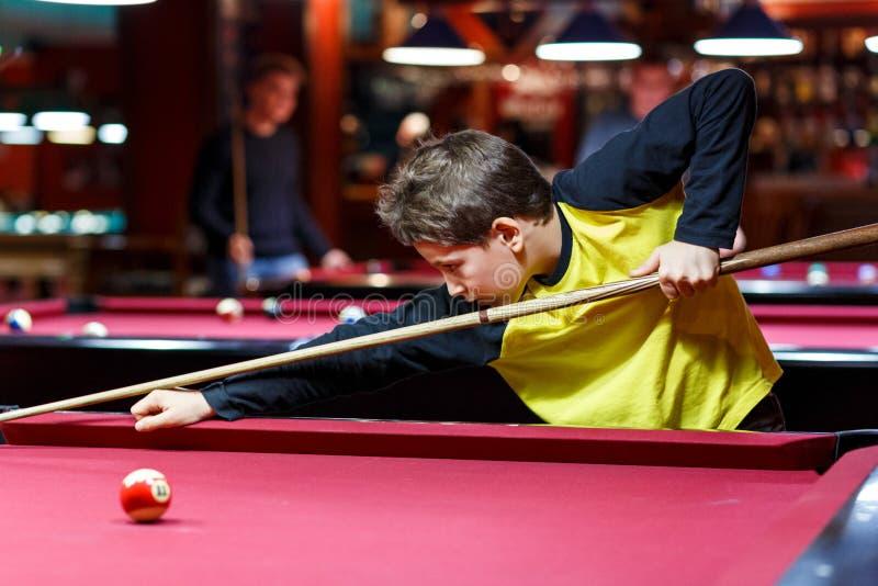 Śliczna chłopiec w żółtych t koszulowych sztukach bilardowych lub basen w klubie Dzieciak uczy się bawić się snooker Chłopiec z b zdjęcia royalty free