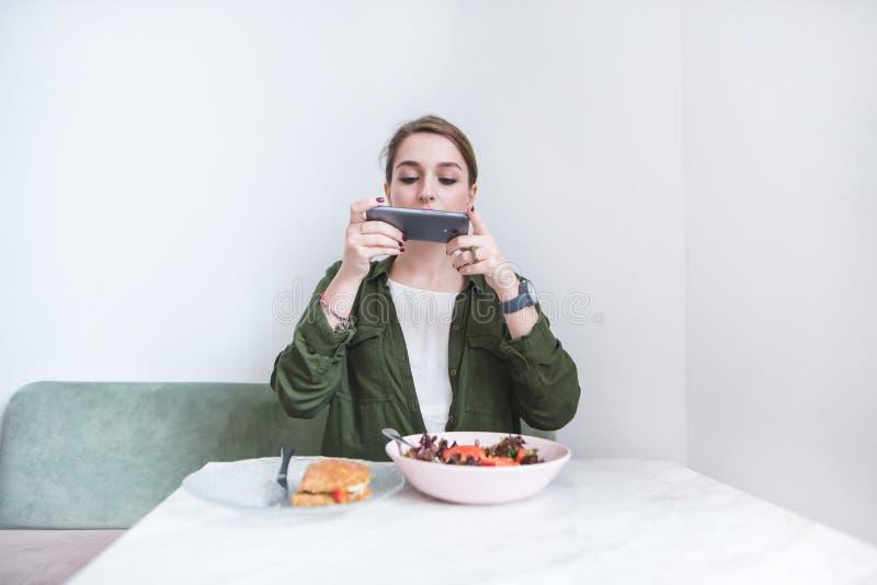 śliczna dziewczyna siedzi przy restauracją przy stołem i bierze fotografię jej jedzenie na kamerze smartphone zdjęcie royalty free