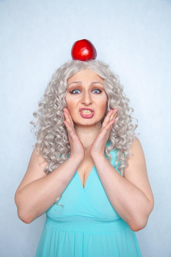 Śliczna dziewczyna z dużym czerwonym Apple na jej głowie na białym stałym Pracownianym tle zdjęcia stock