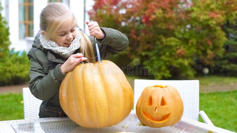 Śliczna emocjonalna dziewczyna rzeźbi dyniowego lampion excited z proces Halloween zdjęcia royalty free