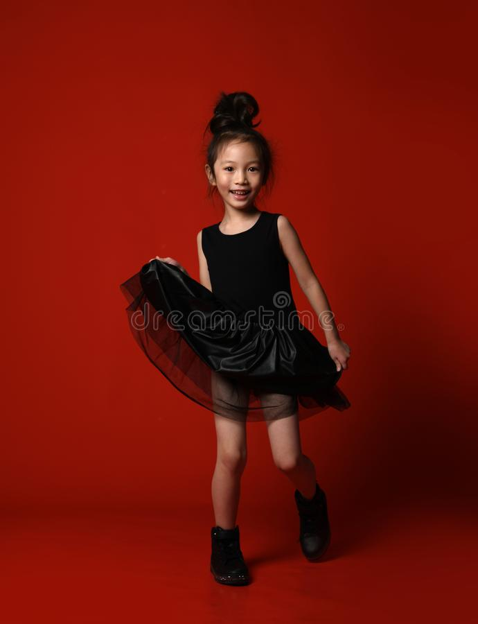 Śliczna mała azjatykcia dziewczyny balerina w pięknej czerni sukni tanczy szczęśliwy ono uśmiecha się na czerwonym pełnym ciele obrazy stock