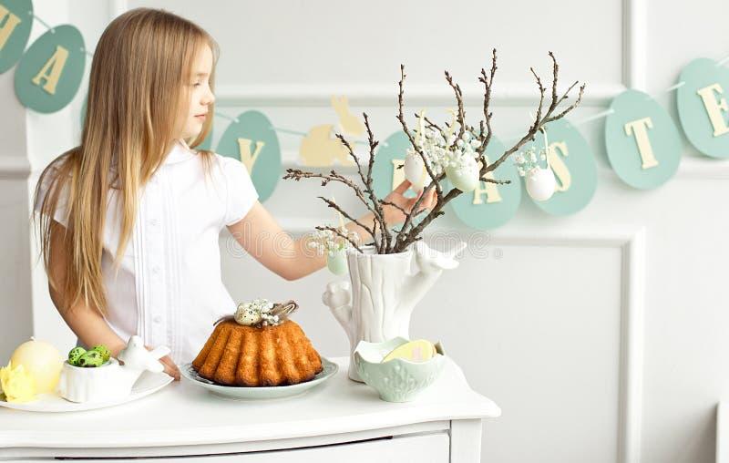 Śliczna mała blondynki dziewczyna jest siedząca przy białym rocznika stołem i patrzeć smakowitego tort z interesem obrazy royalty free