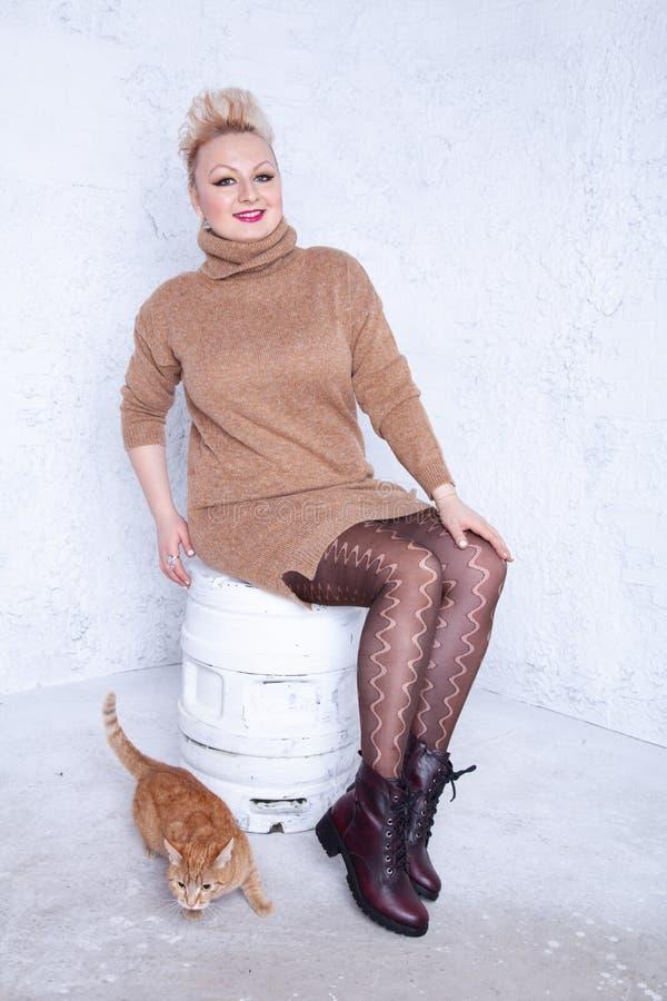 Śliczna pyzata dziewczyna z krótkim włosy w dużym ciepłym brązu pantyhose na białym tle w studiu i pulowerze obraz stock