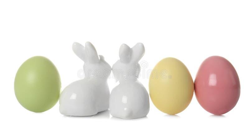 Śliczni ceramiczni Wielkanocni króliki i farbujący jajka na bielu zdjęcia stock