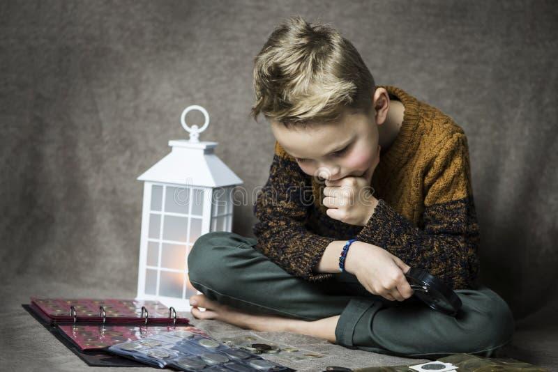 Śliczny chłopiec numizmatyk zbiera stare monety obraz stock